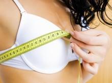 Девушка измеряет размер груди