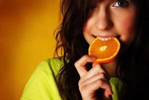 Девушка откусывает апельсин