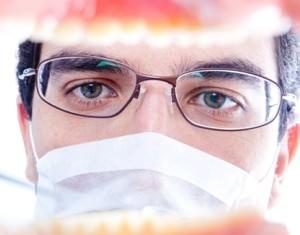 Врач осматривает полость рта пациента