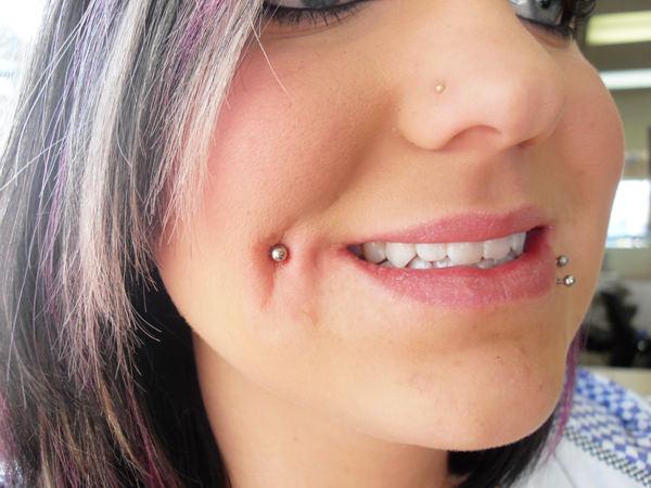 Девушка с пирсингом на щеке