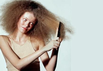 Девушка расчесывает пушистые волосы