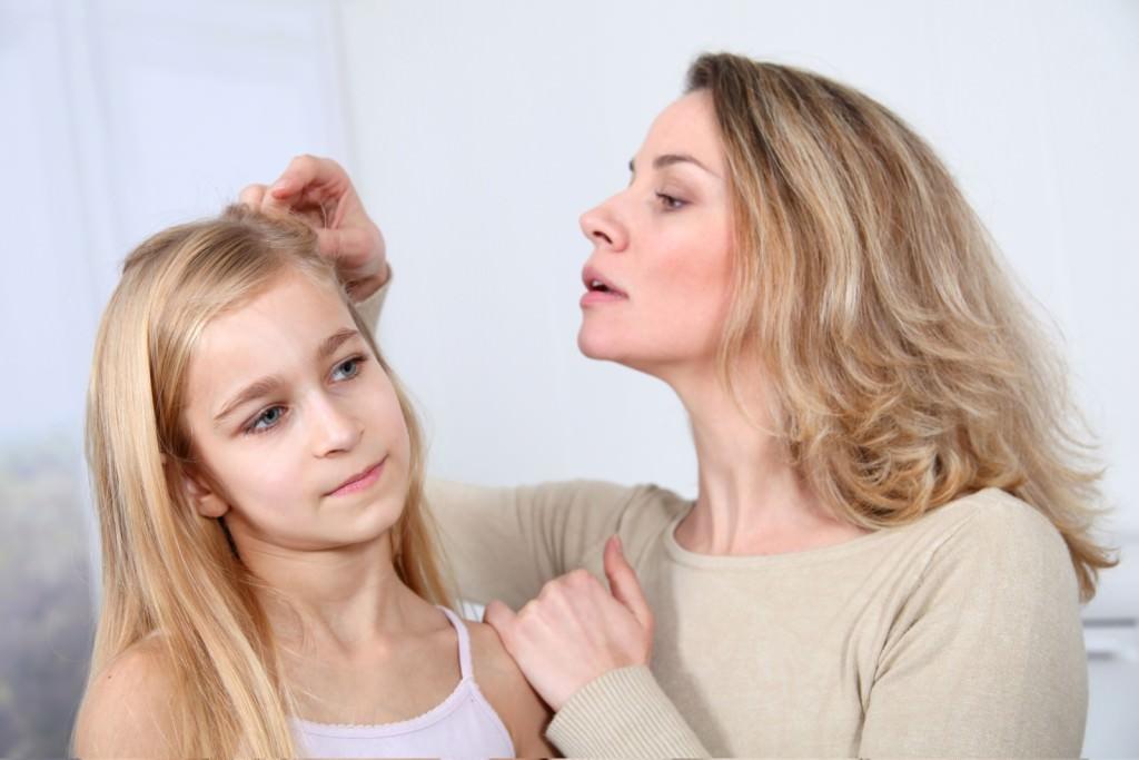 Мама осматривает волосы дочери