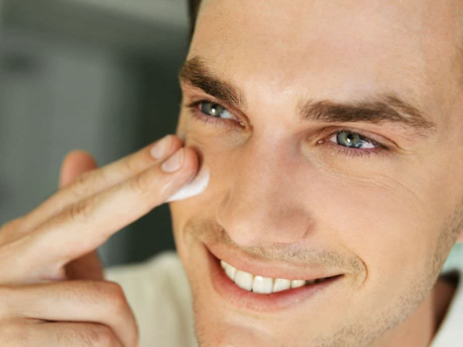 Мужчина наносит крем на лицо