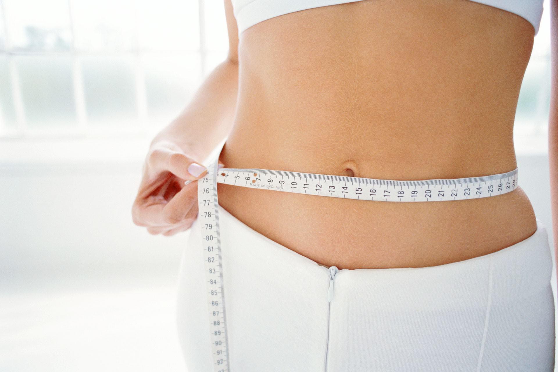 девушка измеряет живот метровой лентой